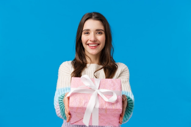 Voici pour vous. joyeuse, charmante et sympathique femme brune souriante, tendant les mains et donnant un cadeau, félicitant pour l'anniversaire, joyeuses fêtes, cadeau fait, debout bleu