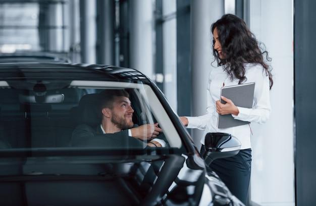 Voici vos clés. client masculin et femme d'affaires moderne dans le salon automobile