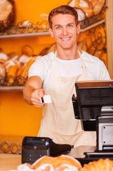 Voici votre carte ! beau caissier étirant la carte en plastique et souriant tout en se tenant dans la boulangerie