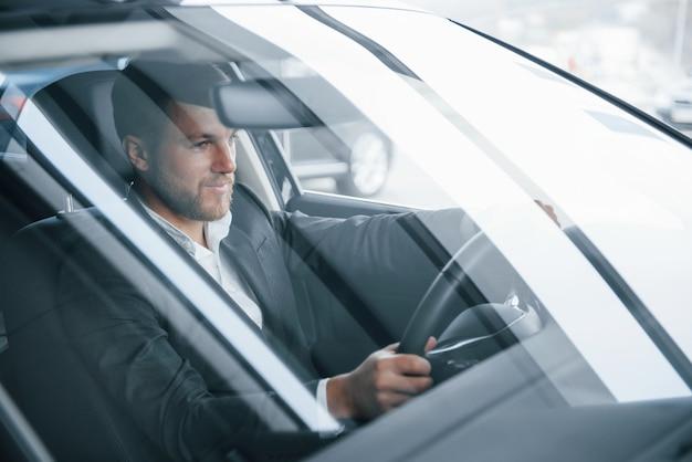 Voilà à quoi ressemble le succès. homme d'affaires moderne essayant sa nouvelle voiture dans le salon automobile