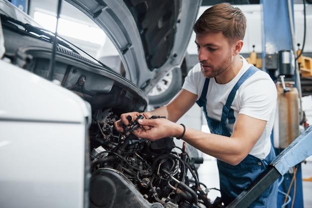 Voilà à quoi ressemble votre transmission. employé dans l'uniforme de couleur bleue travaille dans le salon automobile