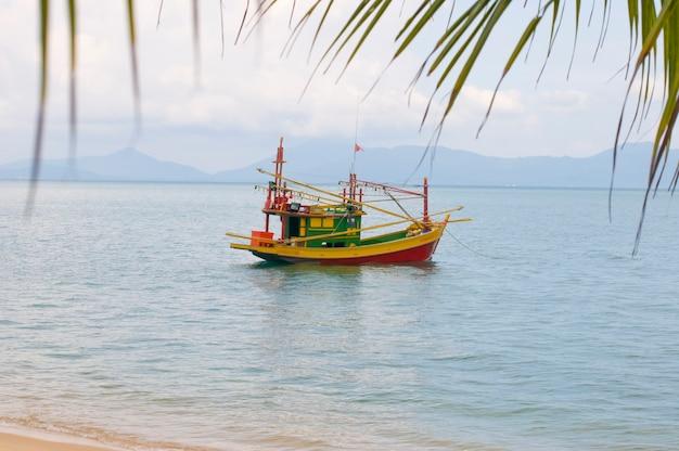Voile bateau de pêche coloré dans l'eau de mer, bateau multicolore dans l'océan tropical peu profond. thaïlande