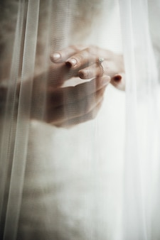 Voile couvre les mains de la mariée avec des alliances