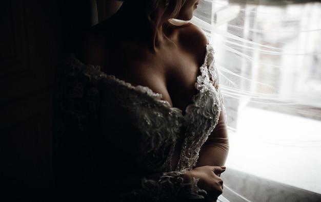 Le voile couvre le visage de la mariée alors qu'elle se tient devant la fenêtre