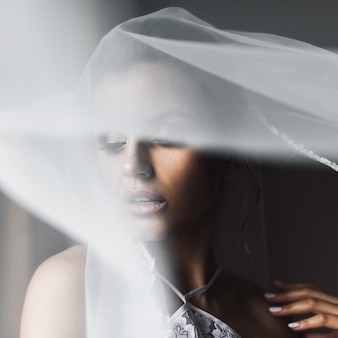 Le voile couvre le visage de la mariée pendant qu'elle se tient devant une fenêtre
