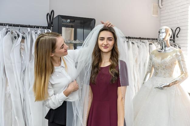Voile de montage vendeuse pour jeune mariée en magasin