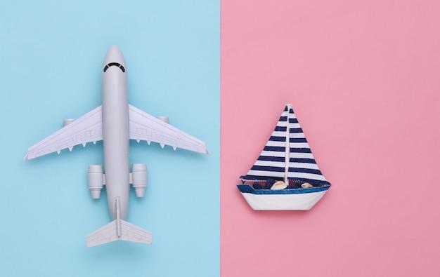 Voilier et avion sur fond rose bleu. concept de minimalisme de voyage. vue de dessus. mise à plat