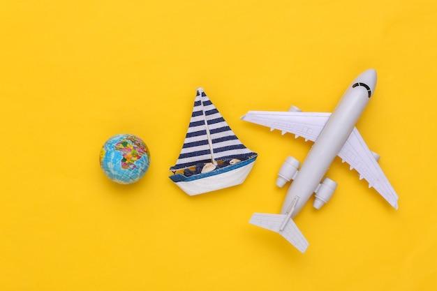 Voilier et avion, globe sur fond jaune. concept de minimalisme de voyage. vue de dessus. mise à plat