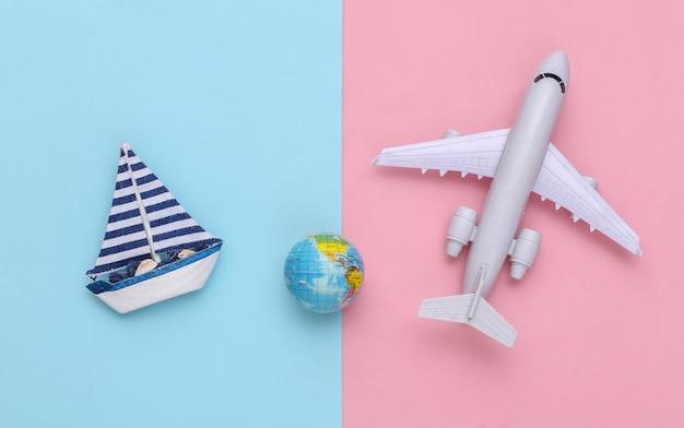 Voilier et avion, globe sur fond rose bleu. concept de minimalisme de voyage. vue de dessus. mise à plat