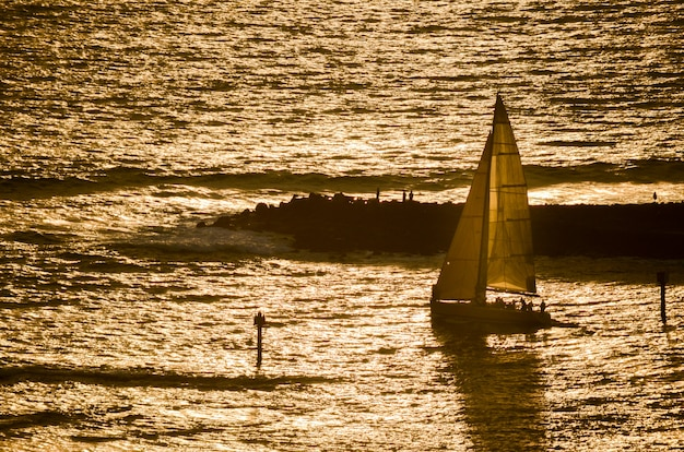 Voilier dirigé au coucher du soleil avec magic island, oahu, hawaii en arrière-plan