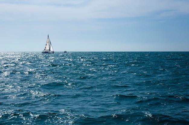 Voilier à l'horizon en mer par une journée ensoleillée