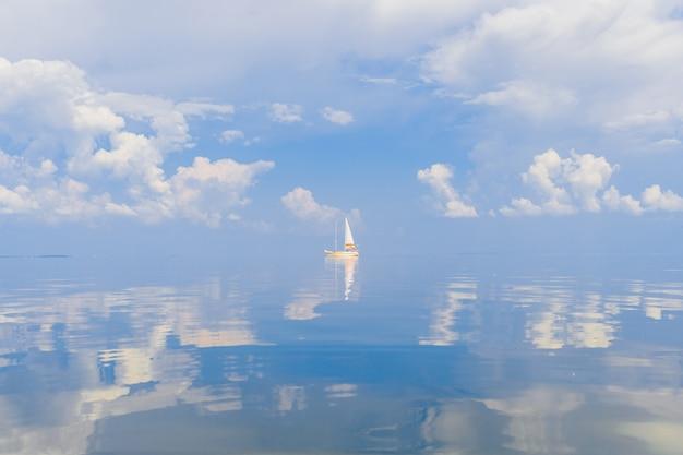 Voilier en mer en journée ensoleillée avec des nuages reflétés dans l'eau.