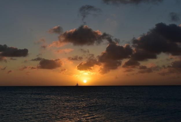 Voilier naviguant devant le soleil couchant à aruba.