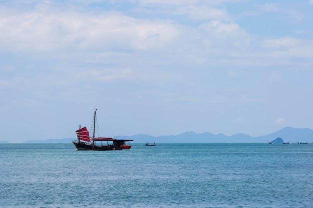 Voilier noir avec voiles rouges naviguant sur la mer bleue