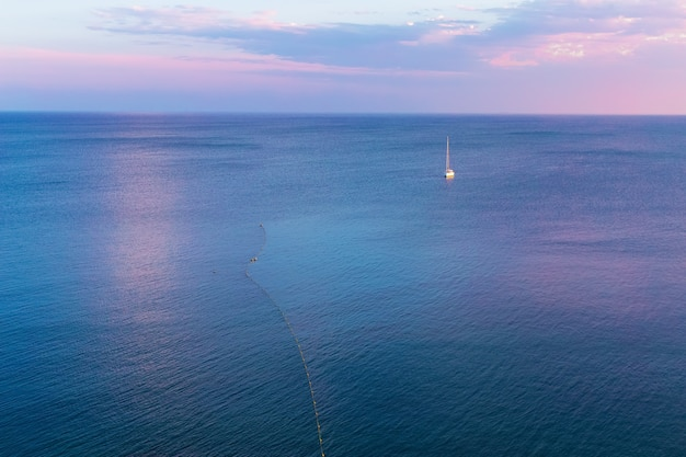 Voilier seul à l'horizon contre la mer bleue calme dans la lumière du soleil du soir du coucher du soleil rose