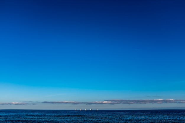 Voiliers sur la ligne d'horizon sur la mer, à la vue depuis la plage de barcelone