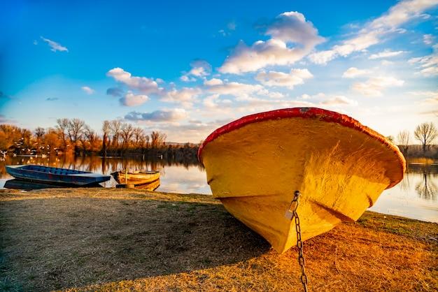 Voir à l'ancien bateau jaune sur le terrain au bord du lac