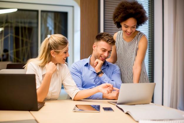Voir au groupe de jeunes gens d'affaires travaillant dans un bureau moderne