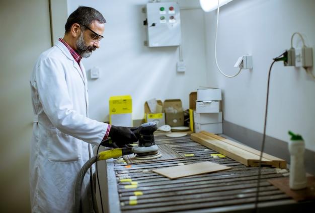 Voir au ingénieur dans le laboratoire examine les carreaux de céramique
