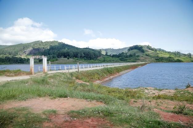 Voir le barrage avec le pêcheur avec beaucoup de soleil d'été brésilien tropical et la natation de chien