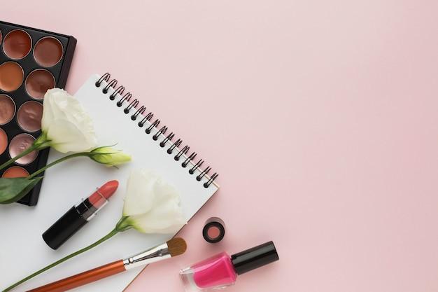 Voir le cadre avec des produits de maquillage et des fleurs