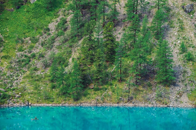 Voir ci-dessus pêcheur en bateau sur l'eau azur du lac de montagne. pêche sur les hauts plateaux. flanc de montagne géant avec forêt au soleil. beau paysage atmosphérique minimaliste de la nature en journée ensoleillée.