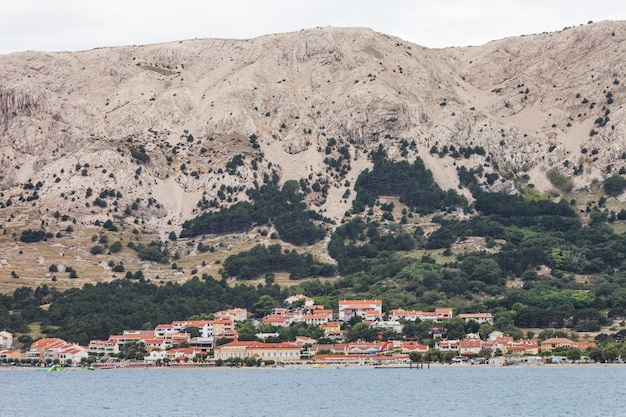 Voir l'île de croatie. paysage ville traditionnelle de croatie avec des toits orange. montagnes à l'arrière-plan. temps nuageux. rive de la mer adriatique.