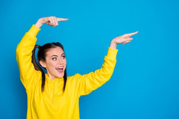 Voir. photo de jolie dame drôle deux queues doigts directs côté espace vide vente bannière commerciale prix bas porter pull à capuche jaune décontracté isolé fond de couleur bleu vif