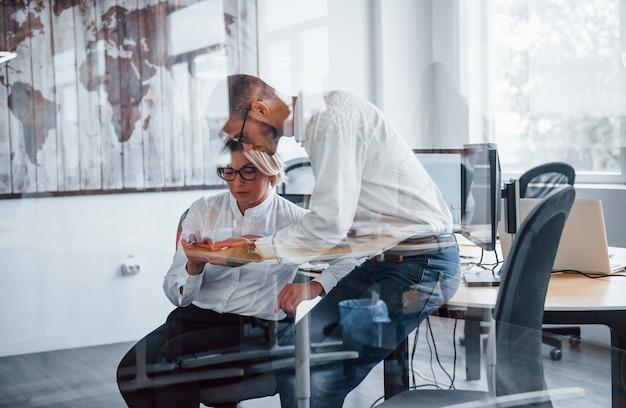 Voir à travers le verre. deux courtiers en vêtements formels travaillent au bureau avec le marché financier.