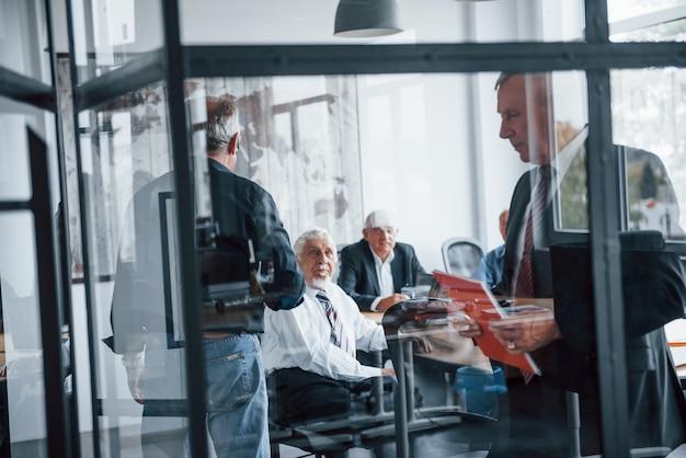 Voir à travers le verre. une équipe âgée d'architectes d'affaires âgés a une réunion au bureau.