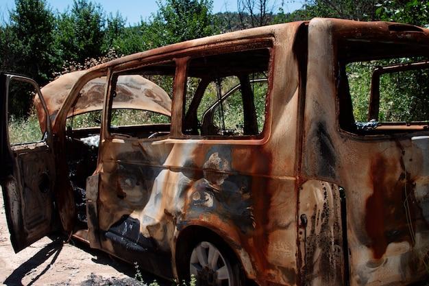 Voiture abandonnée et incendiée au milieu de la forêt