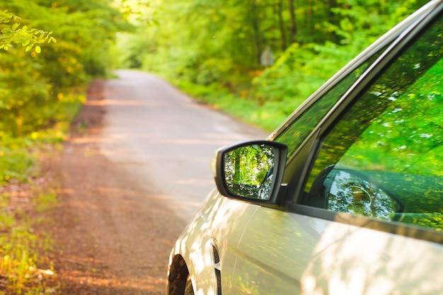 Voiture argentée debout sur le bord de la route dans les bois. vue de côté