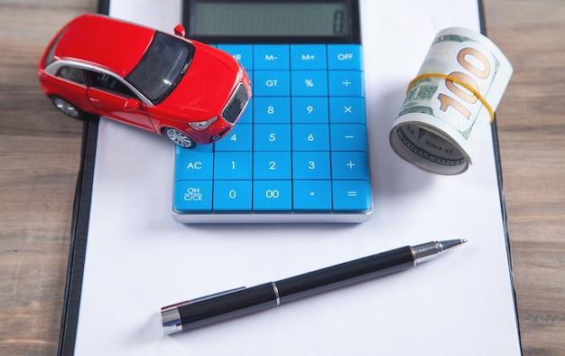Voiture, billets en dollars, calculatrice sur le bureau.