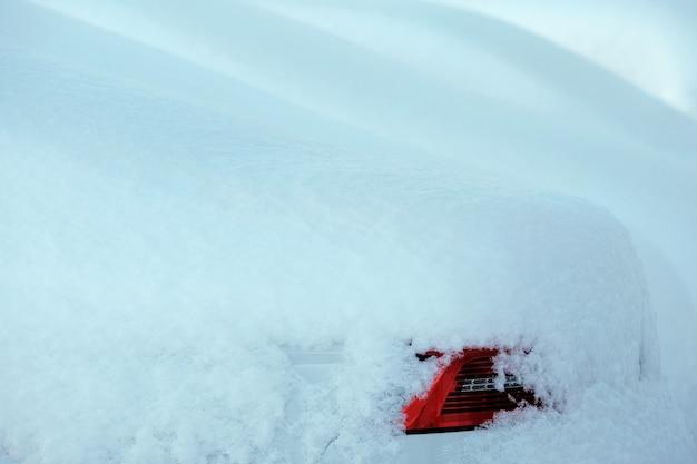 Voiture blanche enneigée et sa lampe arrière rouge fond d'hiver écossais