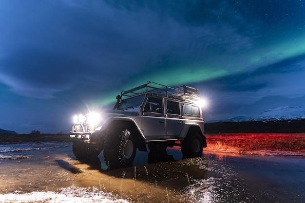 Une voiture blanche posant la nuit