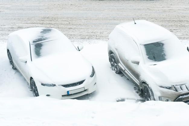 Voiture blanche sous la neige au blizzard