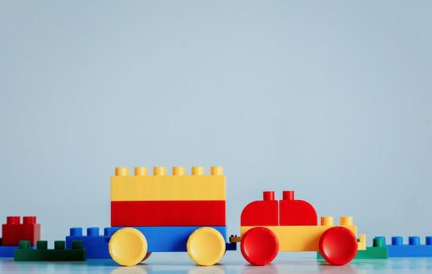 Voiture en briques en plastique aux couleurs jaune et rouge avec remorque