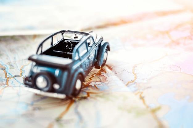 Voiture cabriolet jouet rétro sur la carte, concept de tourisme