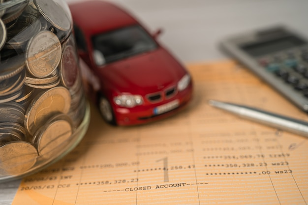 Voiture et calculatrice avec des pièces sur fond de banque de livres financement de prêt de voiture économiser de l'argent