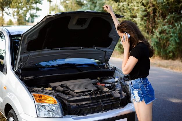 Voiture cassée au bord du chemin. jeune fille appelle le service de voiture pour amener sa voiture à la station de réparation