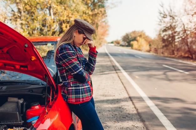 Voiture cassée. femme triste debout sur la route près de son auto à capuche ouverte attendant l'aide
