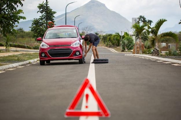 Voiture cassée avec une roue de secours et le signe sur le fond des montagnes