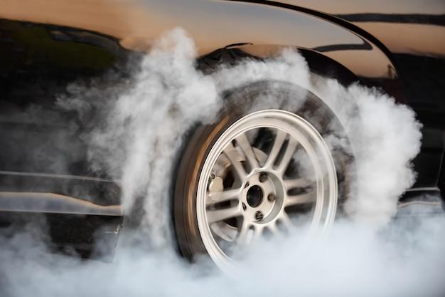 Une voiture de course brûle du caoutchouc de ses pneus en préparation de la course