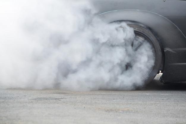 Voiture de course pneu en caoutchouc brûlant sur roue tournante avec fumée blanche