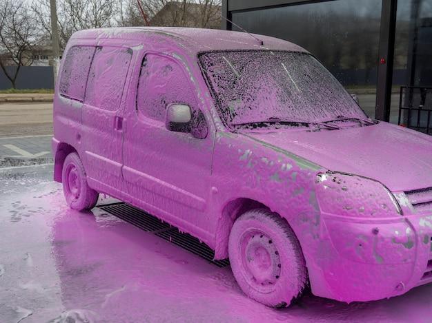 Voiture couverte de mousse rose dans un lave-auto en libre-service