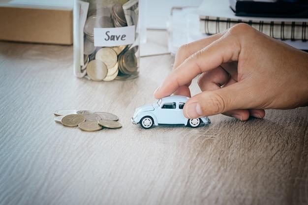 Voiture dans la main des hommes sur le bureau avec pièce d'argent estompée dans la banque d'épargne de pot concept pour les frais d'entretien et les taxes de voiture, filtre de tonalité chaude