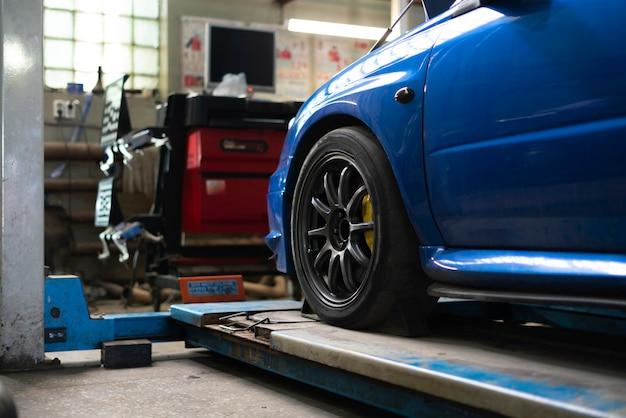 Voiture debout sur une station de relevage dans le garage de service de réparation, atelier intérieur