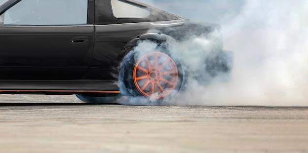 Voiture de dérive de course brûlant des pneus sur piste de vitesse