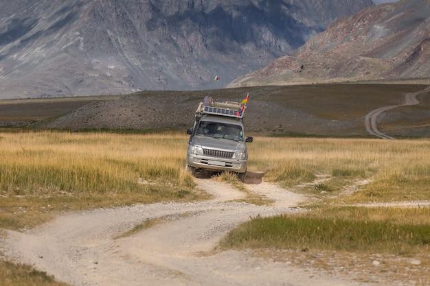 Voiture avec des drapeaux allemands et mongols sur route sinueuse dans les montagnes de l'altaï de mongolie
