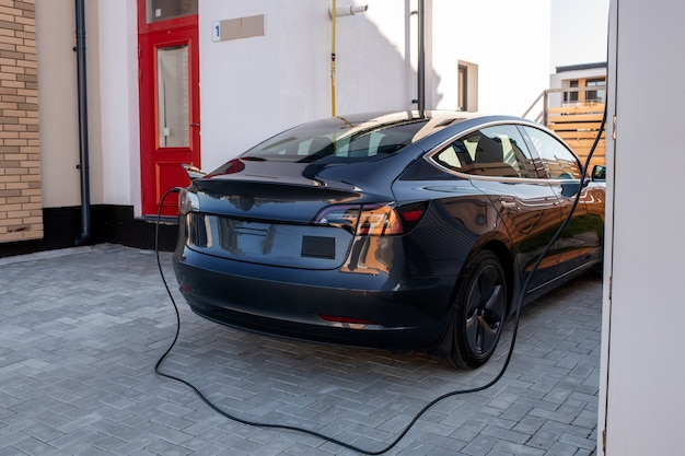 La voiture électrique noire est chargée à la station